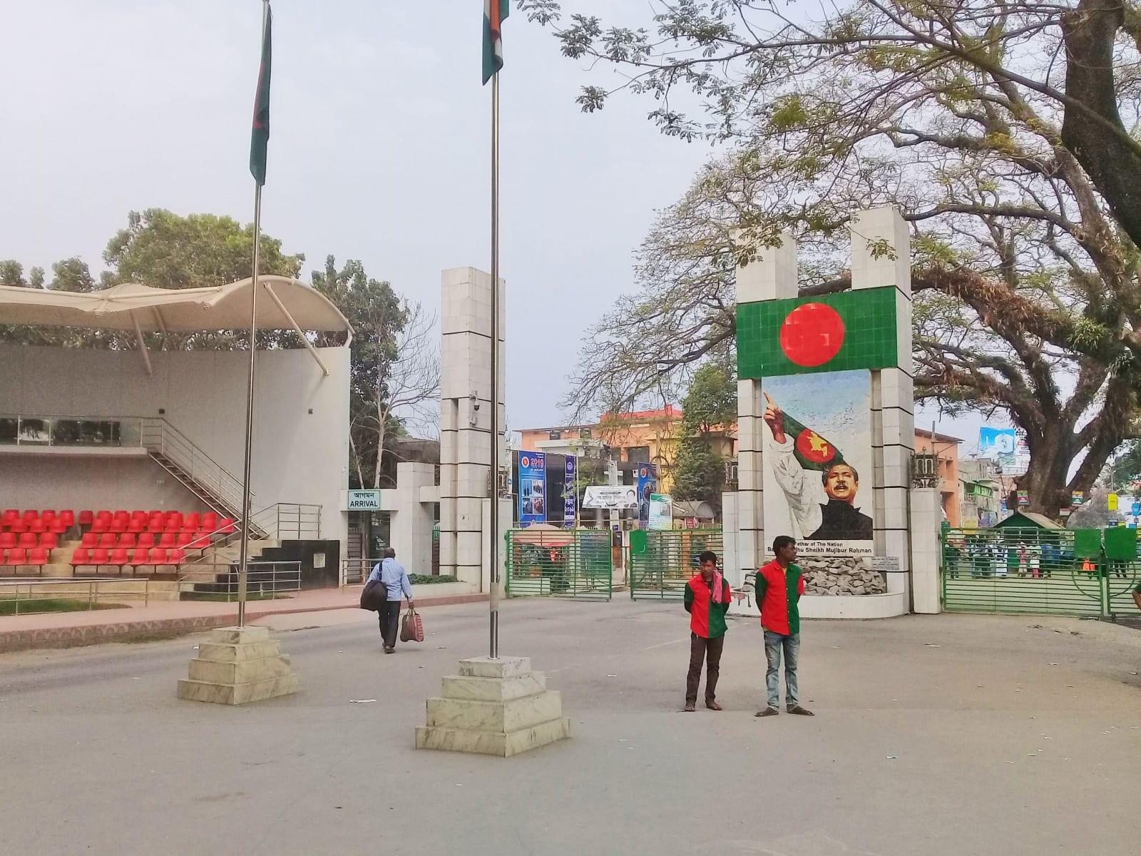 Na hranici - v popředí nosiči zavazadel v národních barvách, v pozadí pod vlajkou Mudžíbur Rahmán, Bangladéš