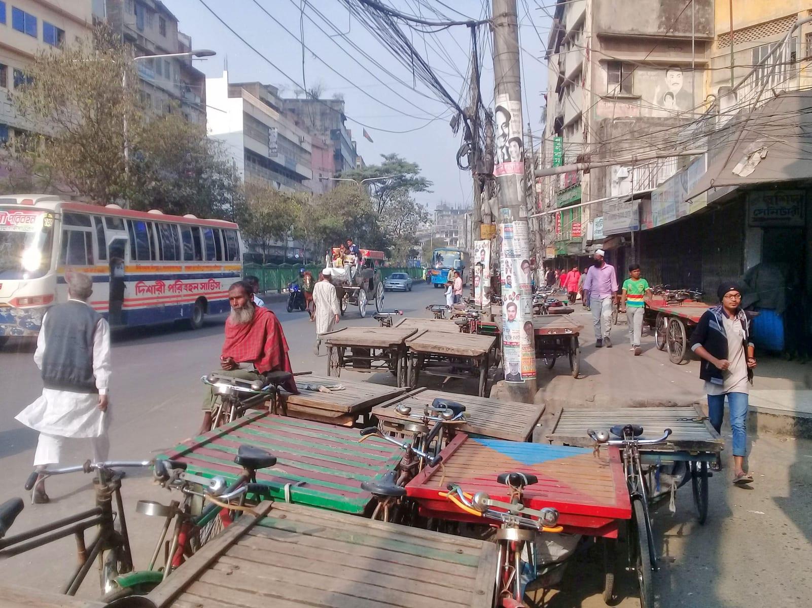Ulice Dhaky, kola s platformou slouží jako transportní prostředek nejen pro zboží, ale i pro pasažéry, Bangladéš